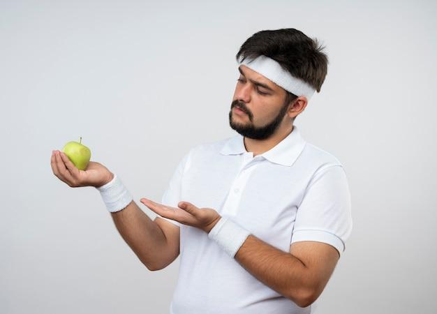 Homem jovem e desportivo descontente com fita na cabeça e pulseira segurando e aponta com a mão na maçã isolada na parede branca