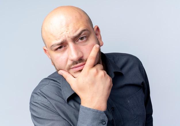 Homem jovem e duvidoso, careca, do call center, colocando a mão no queixo, parecendo isolado no branco