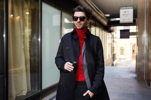 Homem jovem e elegante com cabelos castanhos e cabelos castanhos, óculos escuros, segurando o café para viagem com a mão levantada enquanto caminha pela rua em um dia quente de primavera