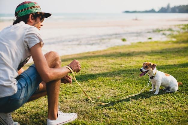 Homem jovem e elegante hippie andando e brincando com um cachorro em uma praia tropical