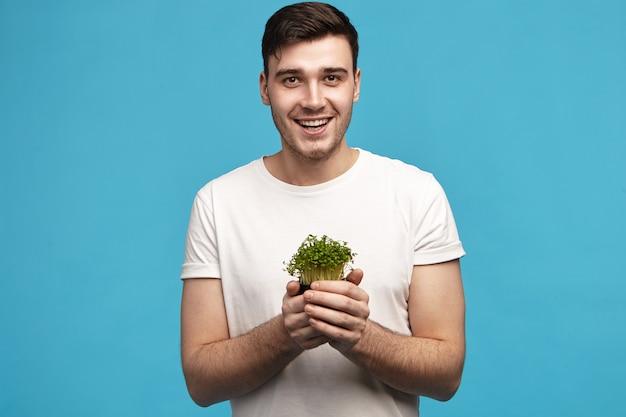 Homem jovem e enérgico com cerdas segurando micro verdes com as duas mãos