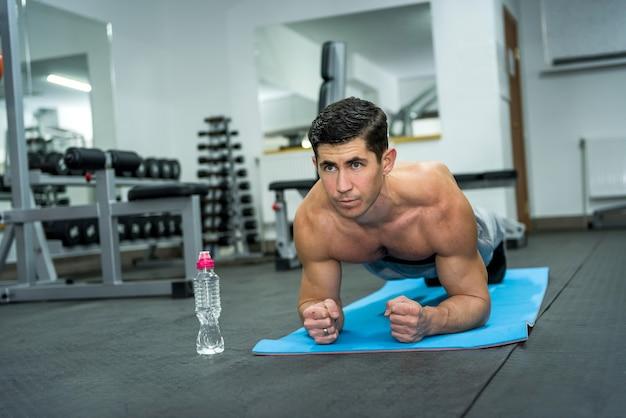 Homem jovem e esportivo fazendo exercícios de prancha na academia