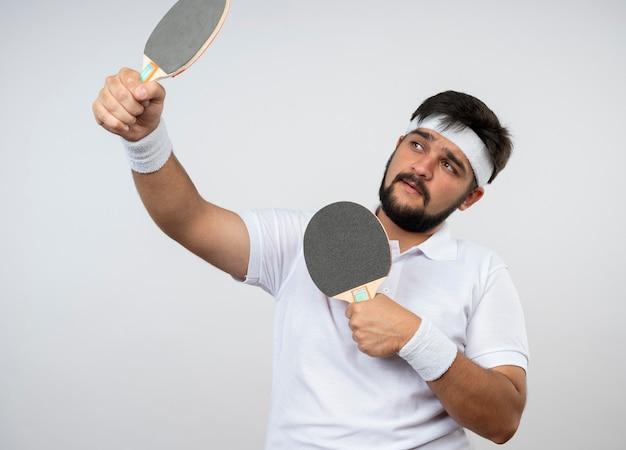 Homem jovem e esportivo satisfeito, olhando para o lado, usando bandana e pulseira segurando uma raquete de pingue-pongue isolada na parede branca