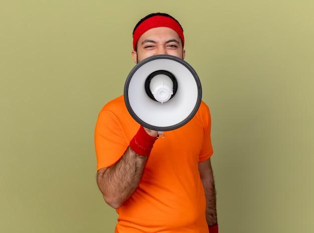 Homem jovem e esportivo satisfeito usando bandana e pulseira falando no alto-falante isolado em verde oliva