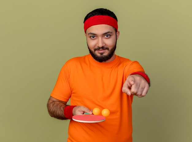Homem jovem e esportivo satisfeito usando bandana e pulseira, segurando uma raquete de pingue-pongue com bolas e mostrando seu gesto isolado em fundo verde oliva