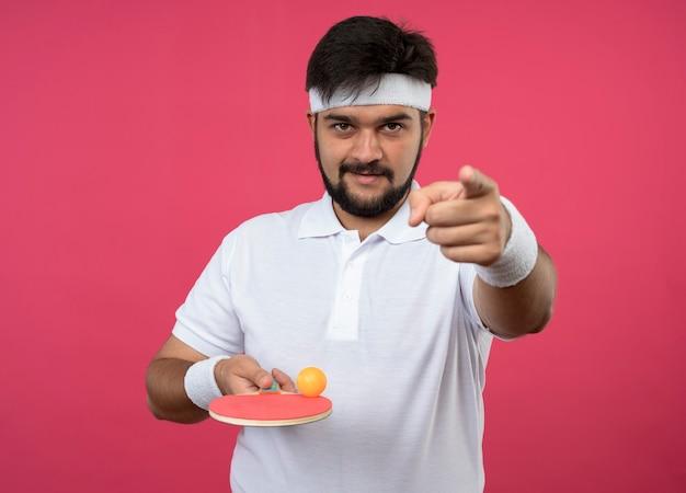 Homem jovem e esportivo satisfeito usando bandana e pulseira segurando uma raquete de pingue-pongue com uma bola mostrando seu gesto