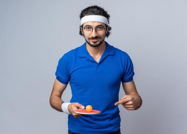 Homem jovem e esportivo satisfeito usando uma faixa na cabeça com uma pulseira segurando e apontando para uma bola de pingue-pongue na raquete