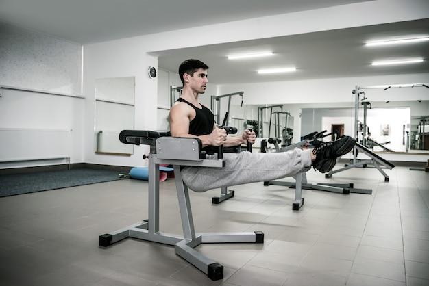 Homem jovem e esportivo treinando na academia