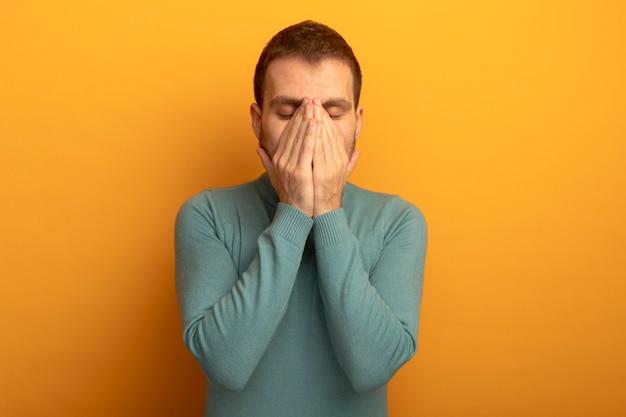 Homem jovem e estressado, caucasiano, mantendo as mãos no rosto com os olhos fechados, isolado em um fundo laranja com espaço de cópia