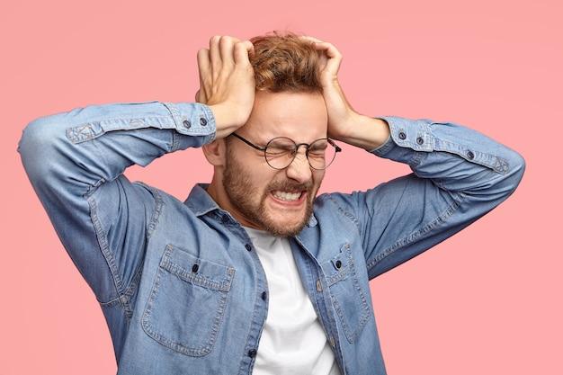 Homem jovem e estressante com a barba por fazer sofre de dor de cabeça, mantém as mãos nas têmporas, cerra os dentes, tem uma dor terrível, fecha os olhos