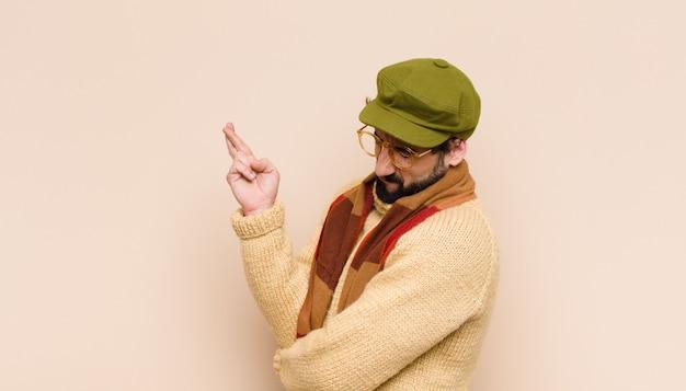 Homem jovem e frio barbudo sorrindo e cruzando os dois dedos ansiosamente, sentindo-se preocupado e desejando ou esperando por boa sorte