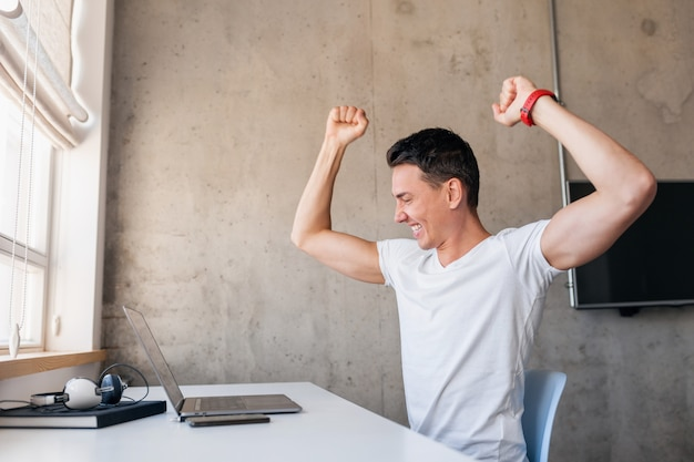 Homem jovem e moderno bonito e sorridente em roupa casual sentado à mesa trabalhando no laptop, freelancer em casa