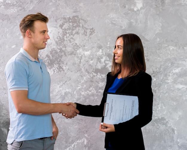 Homem jovem, e, mulher, apertar mão