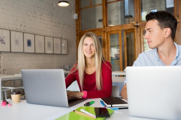 Homem jovem e mulher ocupados trabalhando em um laptop em uma sala de escritório em parceria com espaço aberto
