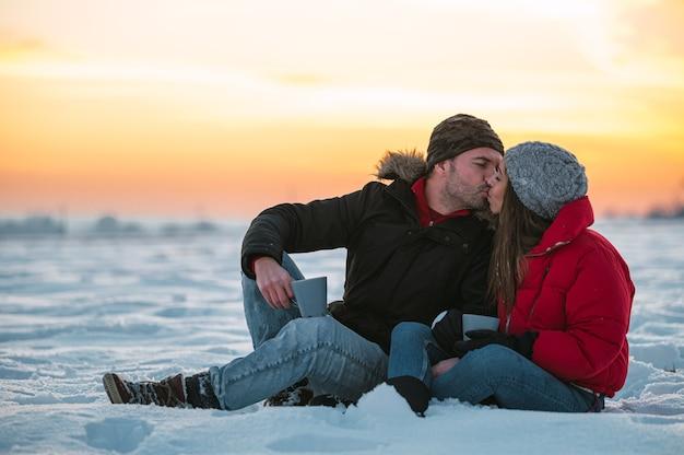 Homem jovem e mulher positivos em trajes quentes com garrafa térmica, sentados na neve e bebendo uma bebida quente no campo