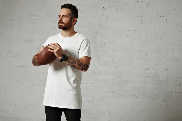 Homem jovem e pensativo, atlético e elegante, com tatuagens e barba, segurando uma bola de rúgbi de couro vintage na parede branca