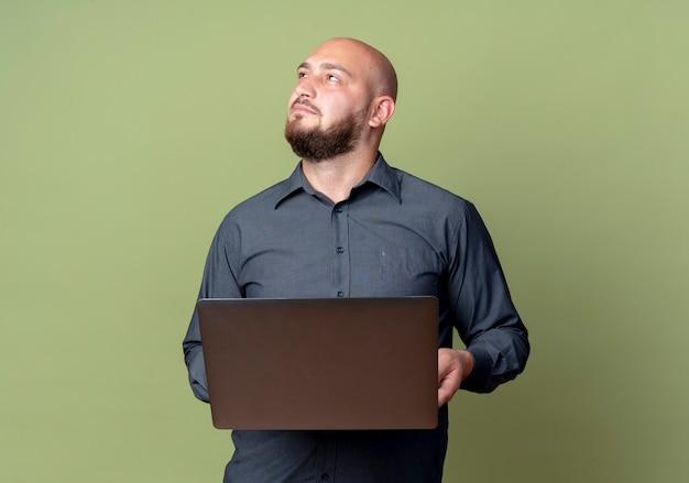 Homem jovem e pensativo, careca, segurando um laptop, olhando para cima, isolado na parede verde oliva