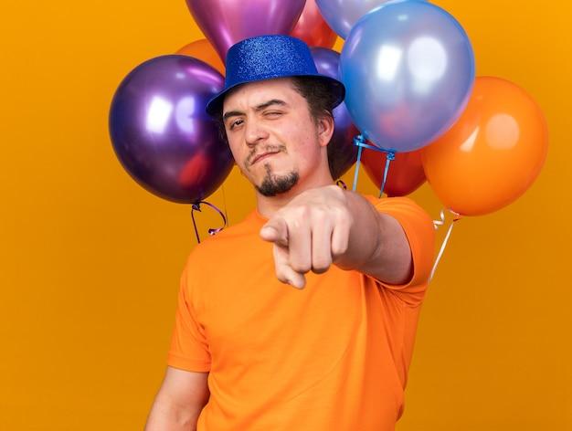 Homem jovem e piscando satisfeito com um chapéu de festa em pé na frente, balões apontando para a frente, isolado na parede laranja