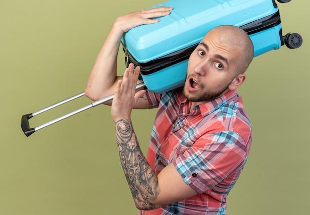 Homem jovem e surpreso viajante caucasiano parado de lado, segurando uma mala no ombro, isolada na parede verde oliva com espaço de cópia