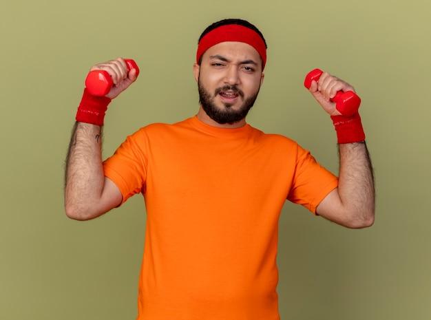 Homem jovem e tenso e esportivo usando bandana e pulseira, fazendo exercícios