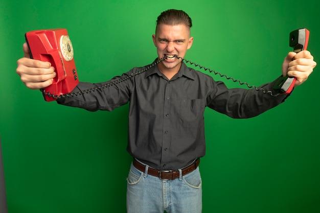 Homem jovem e zangado com uma camisa cinza segurando um telefone vintage, mordendo o fio de pé sobre a parede verde