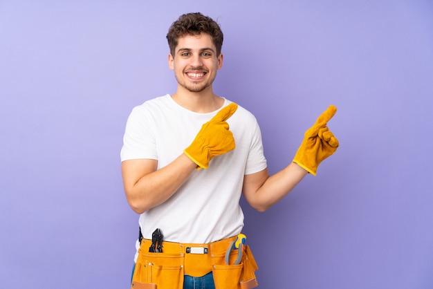 Homem jovem eletricista isolado na parede roxa, apontando o dedo para o lado