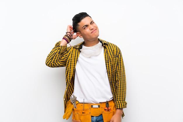 Homem jovem eletricista isolado parede branca com dúvidas e com a expressão do rosto confuso
