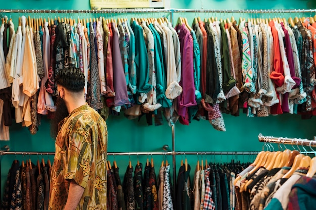 Homem jovem, em, camisa, escolher, roupas, em, shopping, ou, loja roupa