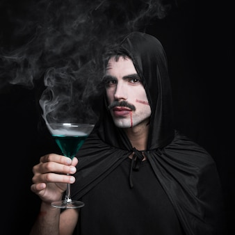 Homem jovem, em, capa, com, capuz, posar, em, estúdio, com, bebida fumegante