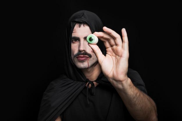 Homem jovem, em, capa preta, com, capuz, mostrando, olho artificial