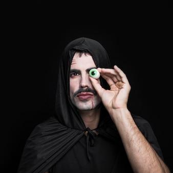 Homem jovem, em, capa preta, com, capuz, segurando, olho artificial