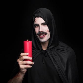 Homem jovem, em, capa preta, com, capuz, segurando vela, e, sorrindo