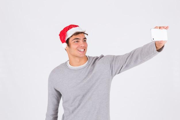Homem jovem, em, chapéu natal, com, smartphone
