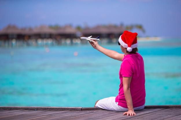 Homem jovem, em, chapéu santa, durante, praia, férias, ligado, madeira, jetty, com, miniatura, de, avião
