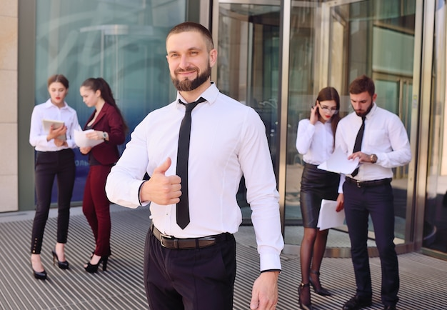 Homem jovem, em, escritório, terno negócio, sorrindo, e, mostrando, polegar, -, sinal, classe