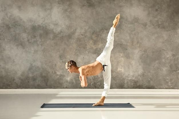 Homem jovem em forma atlética com torso musculoso, sem camisa, praticando ioga asana avançada, em pé com uma perna no chão, treinando equilíbrio, concentração e coordenação, curvando-se para a frente
