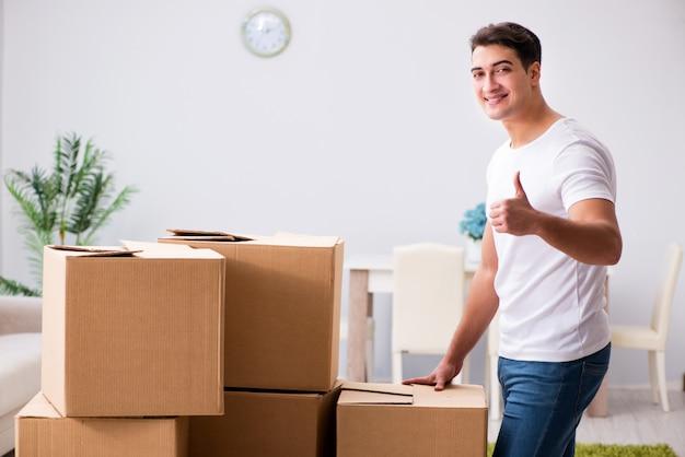 Homem jovem, em movimento, caixas, casa