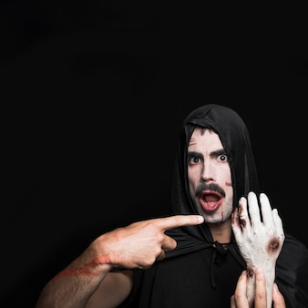 Homem jovem, em, pretas, halloween manto, apontar, em, mão cadáver