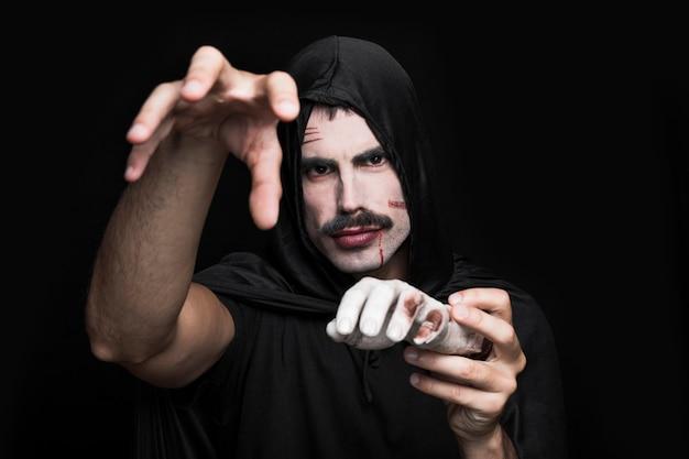 Homem jovem, em, pretas, roupas, posar, em, estúdio, com, mão cadáver
