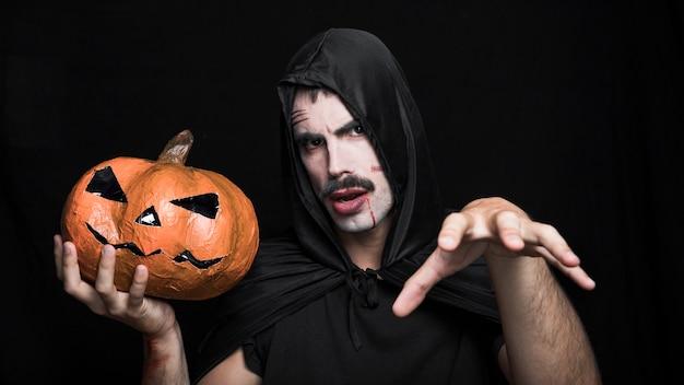 Homem jovem, em, traje dia das bruxas, posar, com, macaco, o'lantern