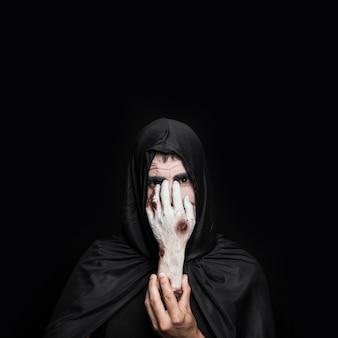 Homem jovem, em, traje halloween, com, capuz, segurando, cadáver, mão