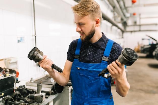 Homem jovem, em, uniforme, segurando, motor, pistões