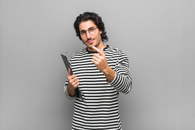 Homem jovem empregado segurando um inventário apontando com o dedo para você como se estivesse convidando se aproximar.