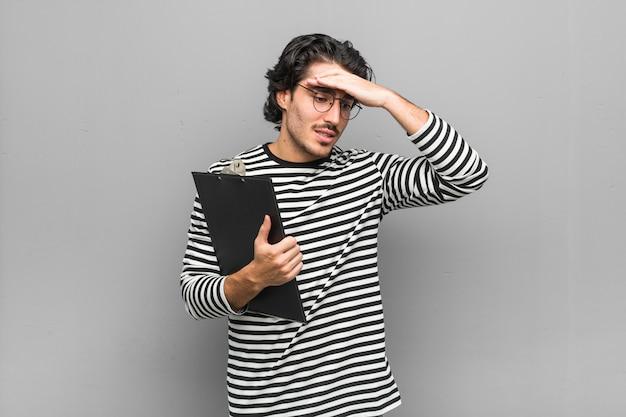 Homem jovem empregado segurando um inventário esquecendo algo, tapa na testa com a palma da mão e fechar os olhos.