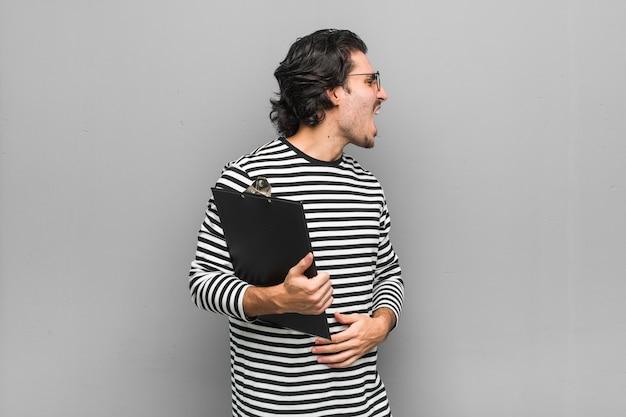Homem jovem empregado segurando um inventário gritando para um espaço de cópia