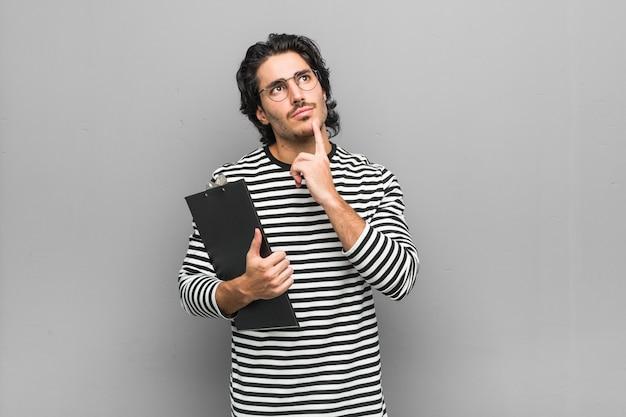 Homem jovem empregado segurando um inventário, olhando de soslaio com expressão duvidosa e cética.