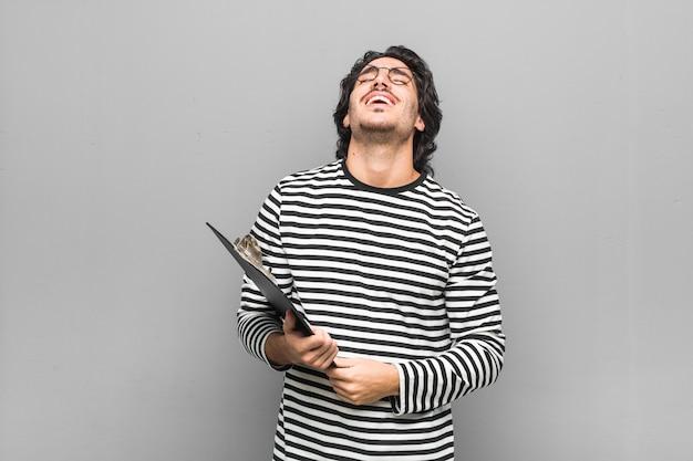 Homem jovem empregado segurando um inventário relaxado e feliz rindo, pescoço esticado, mostrando os dentes