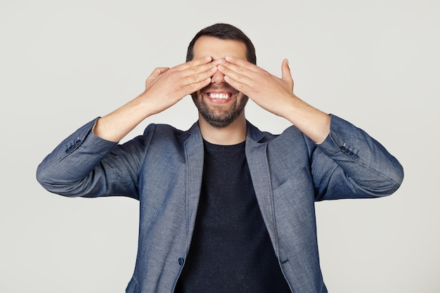 Homem jovem empresário com uma barba com uma jaqueta cobrindo os olhos com as mãos, sorrindo alegre e engraçado.