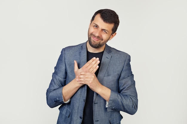 Homem jovem empresário com uma barba em um casaco, sofrendo de dores nas mãos e nos dedos, inflamação da artrite.