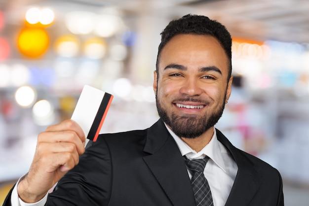Homem jovem empresário de sucesso em um elegante terno clássico preto, segurando um cartão de crédito plástico